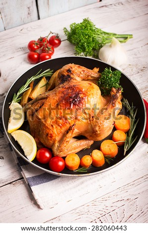 Roasted chicken and vegetables on the wooden table