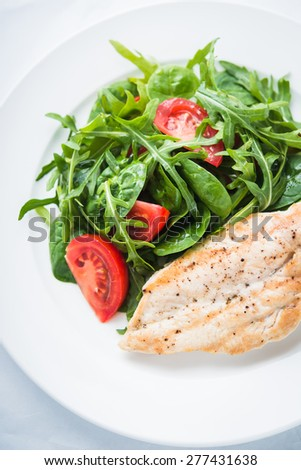 Roasted chicken breast and fresh salad with tomato and greens (spinach, arugula) top view on white textured background. Healthy food. - stock photo