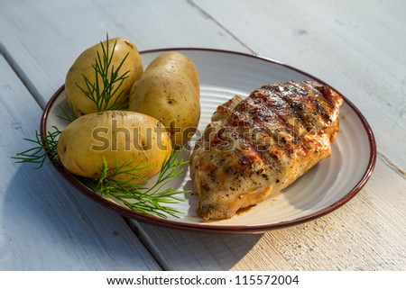 Roasted chicken breast served with potatoes and dill on old plank - stock photo