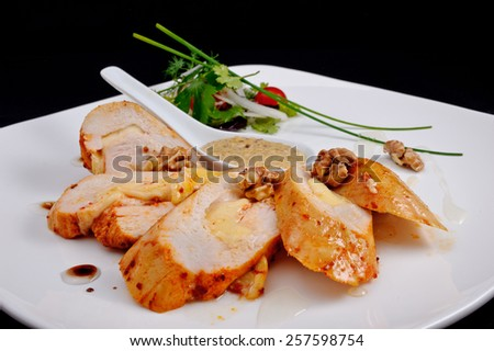 Roasted chicken breast with a golden crust with cheese, walnuts, beige sauce in a saucepan, poured a clear syrup, served with a salad of onion, cherry tomatoes, parsley, dill, green leaves on a plate - stock photo