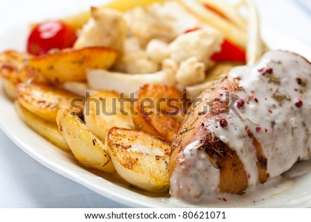 Roasted chicken breast with baked potatoes and herb sauce