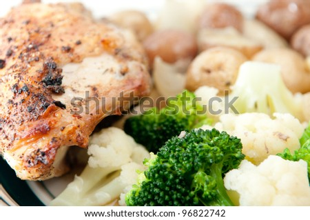 roasted chicken breast with crispy skin, baby red and white potatoes and fresh broccoli and cauliflower - stock photo