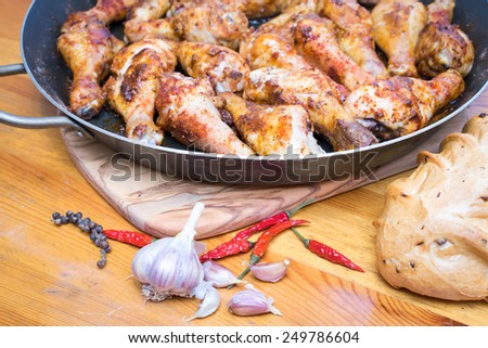 Roasted chicken drumsticks on a frying pan on the cutting board, with garlic and chilly pepper and bread around on a wooden table - stock photo