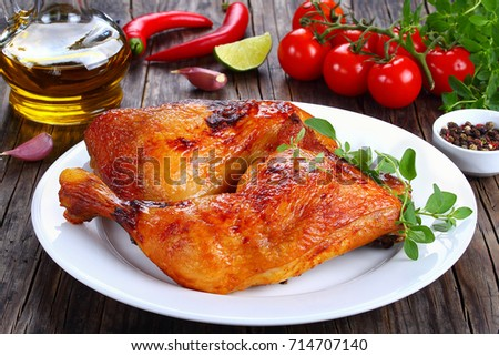 roasted chicken leg quarters with crispy golden brown skin with fresh green thyme leaves on white plate, on dark wooden table with tomatoes,  bottle of olive oil, garlic, view from above, close-up