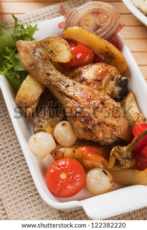 Roasted chicken leg with potatoes, onion and tomato