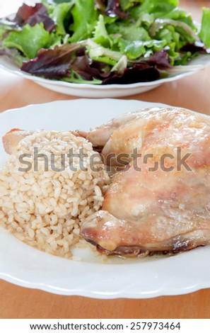Roasted chicken leg with rice and salad - stock photo