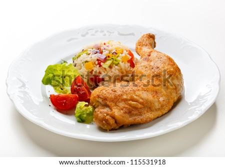 Roasted chicken leg with rice and vegetables - stock photo