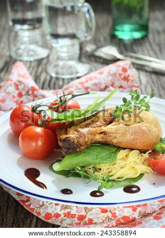 Roasted chicken leg with spaghetti, green leaves, tomatoes and sauce. selective focus - stock photo