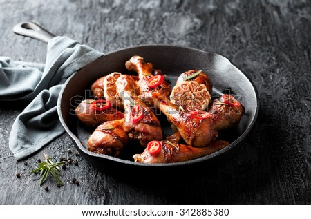 Roasted chicken legs in cast iron skillet, selective focus - stock photo