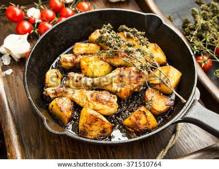Roasted chicken legs with baked potatoes garnish and herbs in a cooking pan - stock photo