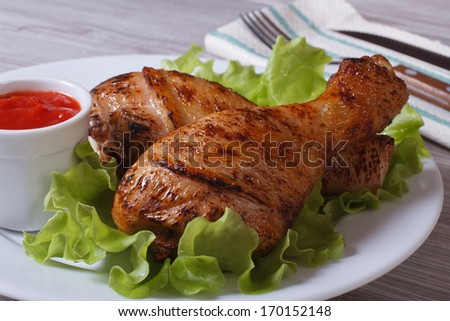 roasted chicken legs with lettuce and ketchup on a white plate - stock photo