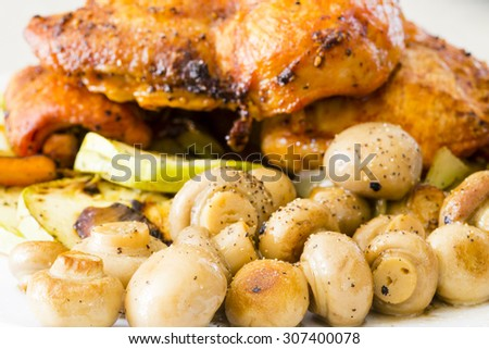 Roasted chicken legs with mushrooms - stock photo