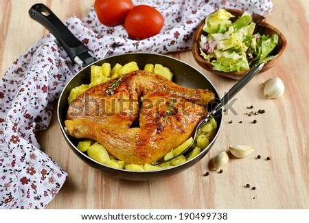 Roasted chicken legs with potatoes on wooden background with tomatoes, garlic and pepper. Selective focus