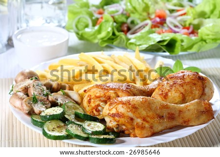 Roasted chicken legs with vegetables - stock photo