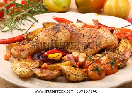 Roasted chicken legs with vegetables and herbs on wooden background - stock photo