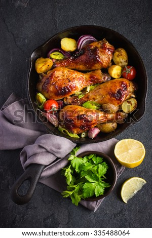 Roasted chicken legs with vegetables on cast iron pan, top view - stock photo
