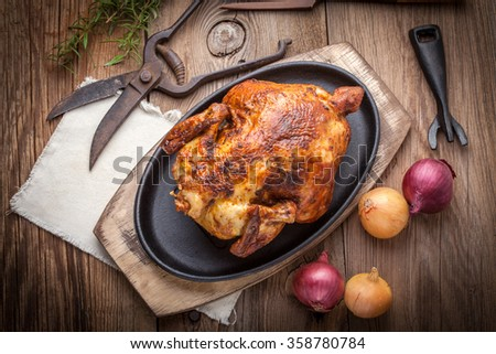 Roasted chicken on a spit on cast iron pan. - stock photo