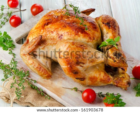 Roasted chicken on wooden table. Selective focus - stock photo