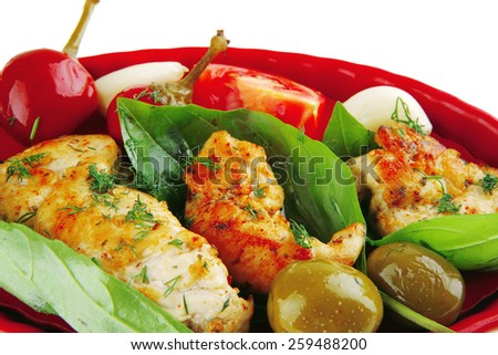 roasted chicken pieces served with vegetables on red - stock photo