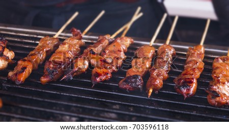 roasted chicken sate sticks lined up a hot barbecue