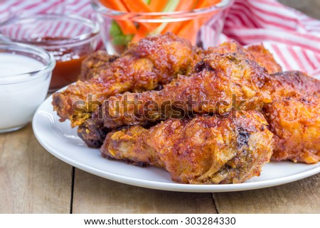 Roasted chicken served with celery and carrot sticks, blue cheese dressing and hot sauce - stock photo
