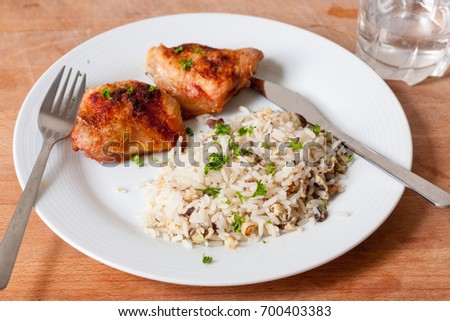 Roasted chicken thighs and mushroom rice on a white plate