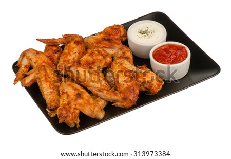 Roasted chicken wings on the black plate isolated. - stock photo