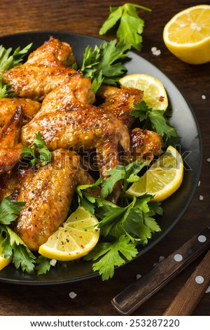 Roasted chicken wings with parsley and lemon on black plate - stock photo