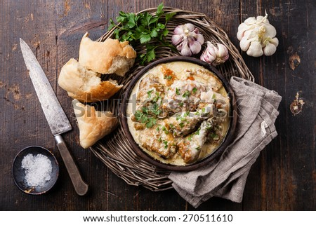 Roasted chicken with creamy garlic sauce in clay pan ketsi on dark wooden background - stock photo