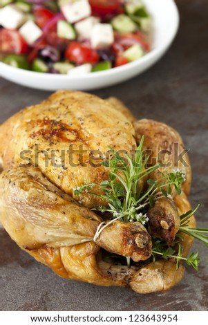 Roasted chicken with fresh herbs.  Dish of Greek salad behind. - stock photo
