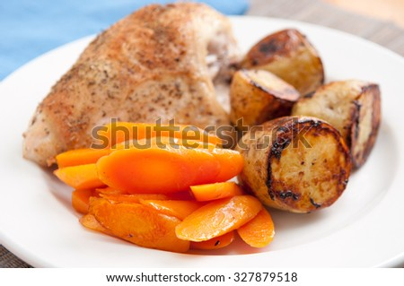 roasted chicken with fried potatoes and carrots for a holiday meal stock photo - stock photo