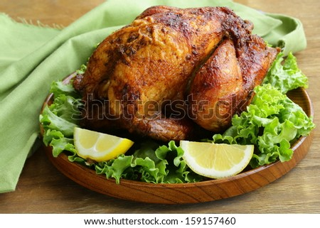 roasted chicken with herbs served on a plate with lemon - stock photo