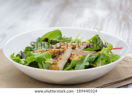 roasted chicken with mix salad in white bowl on wood table