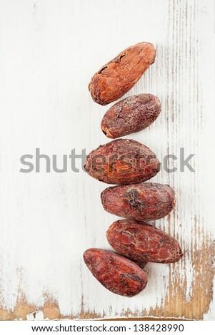 roasted cocoa chocolate beans on white wood background - stock photo