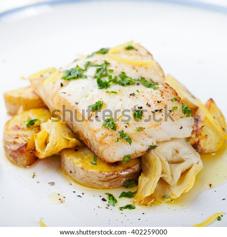 Roasted cod, codfish with baked potatoes and artichokes with lemon and herbs sauce on a white background - stock photo