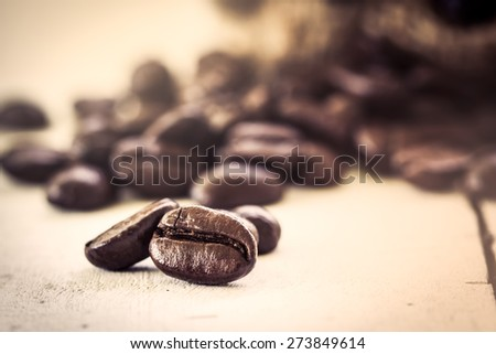 Roasted coffee bean on wooden background in vintage color style - stock photo