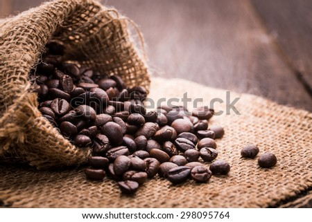 Roasted coffee bean spill out from bag. - stock photo
