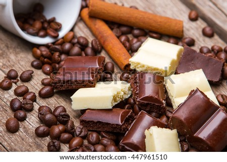 Roasted coffee beans and chocolate. White chocolate and cinnamon stick. Part of morning dessert. Snack for sweet tooth. - stock photo