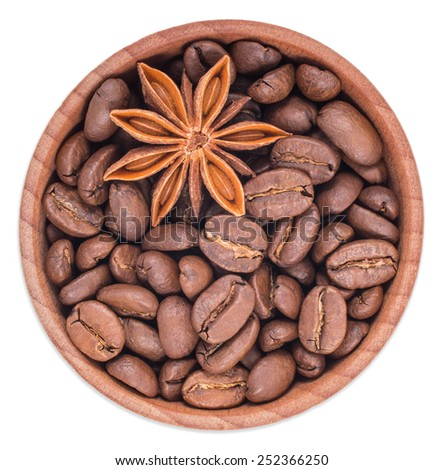 Roasted coffee beans and star anise in a wooden bowl isolated on white background top view. - stock photo