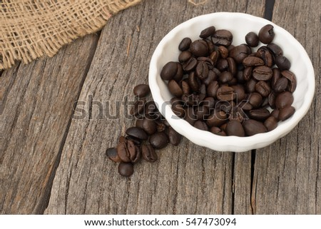 Roasted coffee beans(c.arabica) inside a round white bowl with burlap
