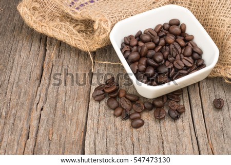Roasted coffee beans(c.arabica) inside a square white bowl with burlap