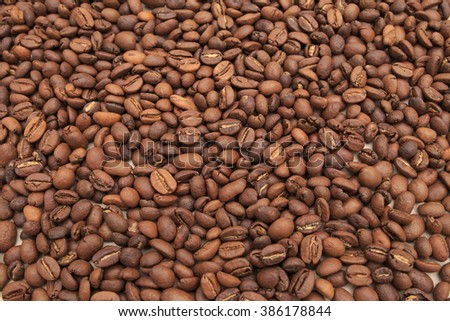 Roasted coffee beans, can be used as a background. A lot of coffee beans on kraft paper.Brown coffee beans for background and texture.Arabic roasting coffee - ingredient of hot beverage.