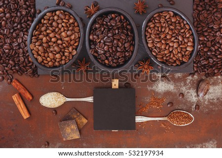 Roasted coffee beans, dark chocolate, spices and blank tag on a rustic background. Top view, blank space, vintage toned image