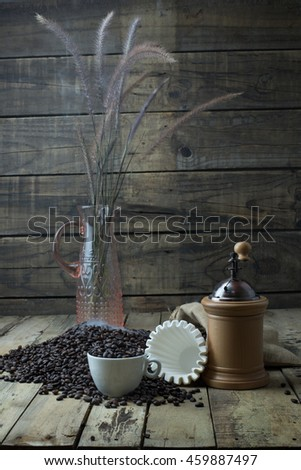 Roasted coffee beans in a bag And roasted coffee beans in a coffee cup. With a paper coffee filter And coffee grinders Up on the a wooden board