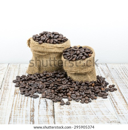 Roasted coffee beans in a sack on a wooden background - stock photo