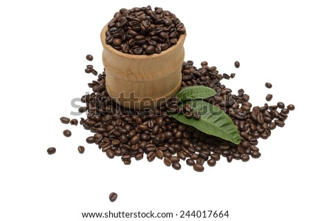 Roasted coffee beans in a wooden bowl and decoration of green leaves orange. - stock photo