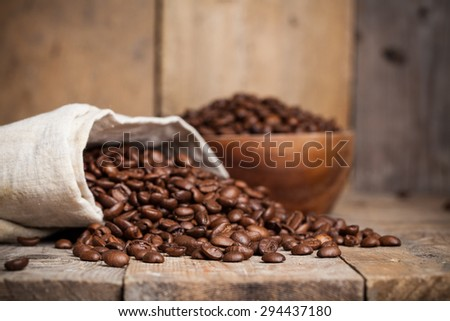 Roasted coffee beans in a wooden bowl on wooden background