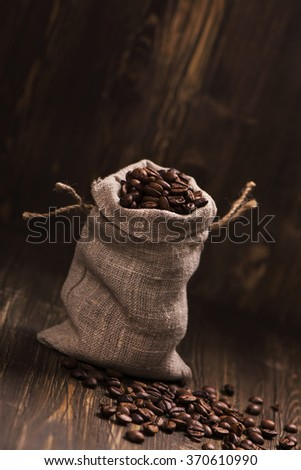 Roasted coffee beans in burlap bag over wooden background. Vintage style. Toned image. Selective focus - stock photo
