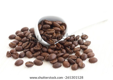 Roasted coffee beans in ceramic measuring scoop. On fabric.