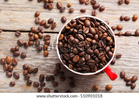 Roasted coffee beans in cup on a grey wooden table